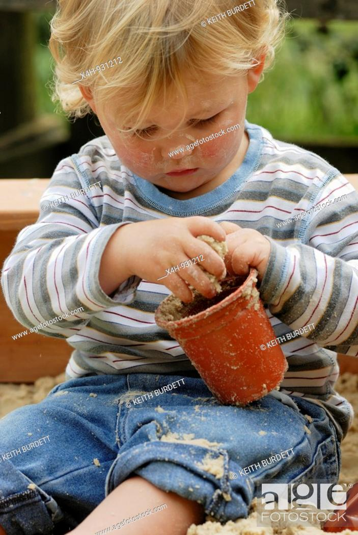 Stock Photo: Small boy playing with a flowerpot in a sandpit.