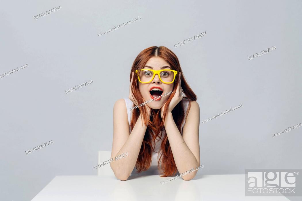 Stock Photo: Surprised Caucasian woman sitting at table wearing yellow eyeglasses.