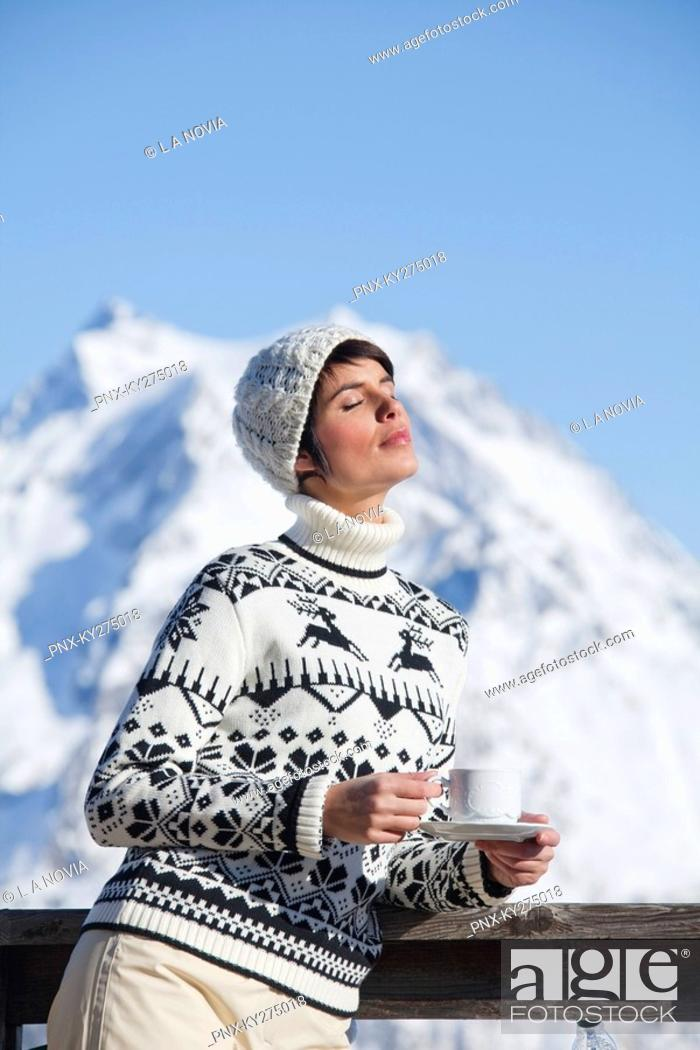 Stock Photo: Young woman with coffee cup, enjoying winter sun, mountains in background.