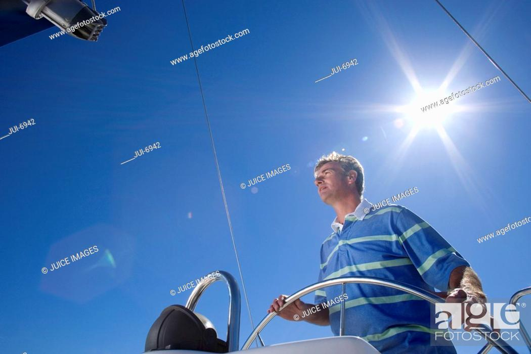 Stock Photo: Man in striped blue polo shirt standing at helm of sailing boat out at sea, steering, low angle view lens flare.