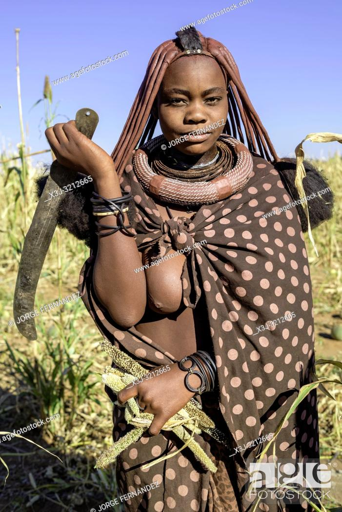 Stock Photo: Portrait of a Himba woman with a machete in a millet field.