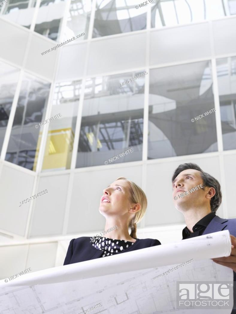 Stock Photo: Two business people holding blueprint low angle view.
