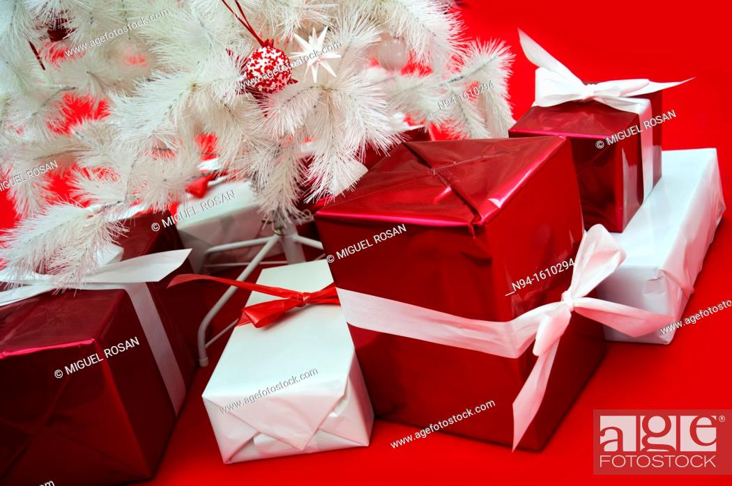Stock Photo: Still white Christmas tree with presents on red carpet.