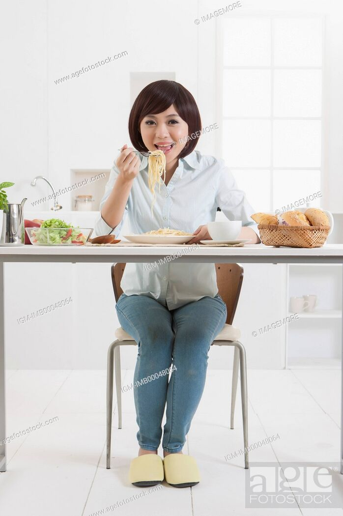 Imagen: Young woman sitting and eating noodle with smile,.