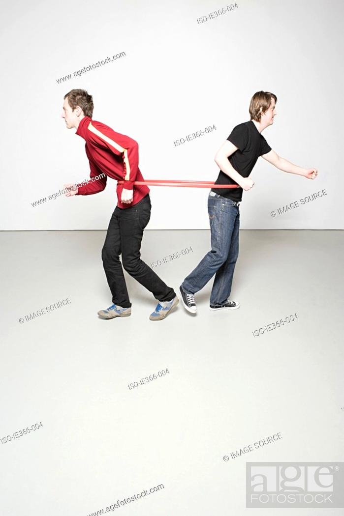 Stock Photo: Two men pulling plastic hoop.
