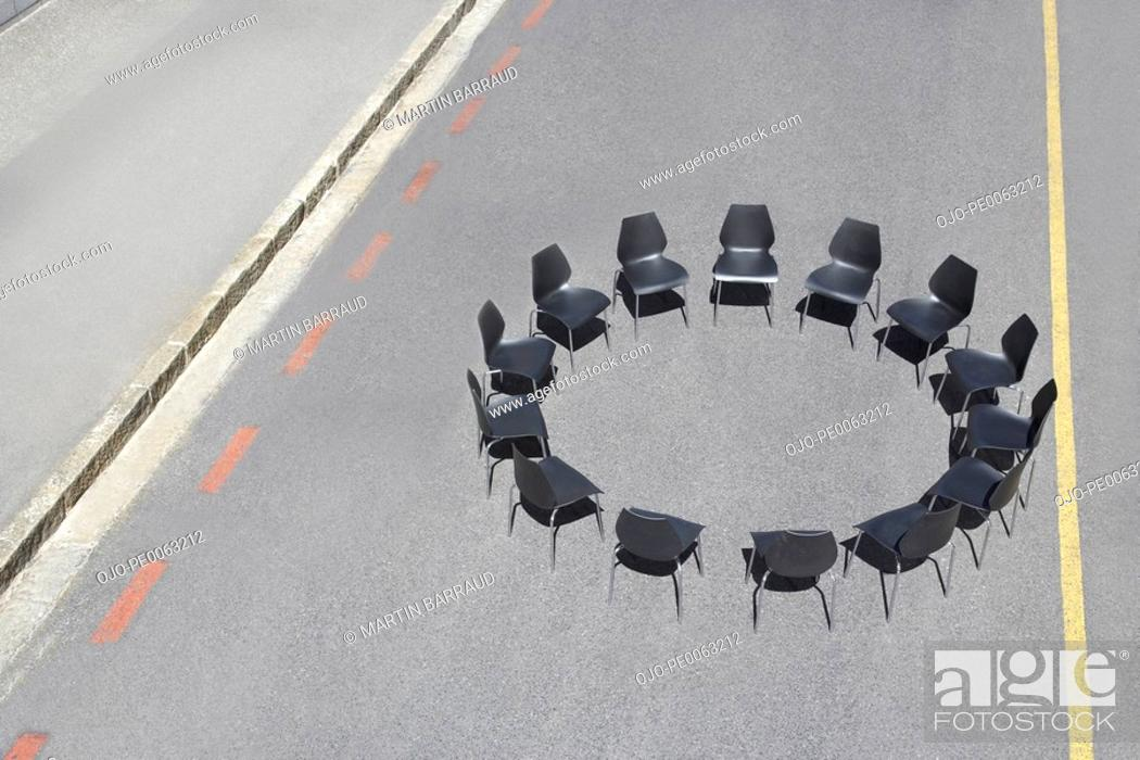 Stock Photo: Circle of office chairs in roadway.