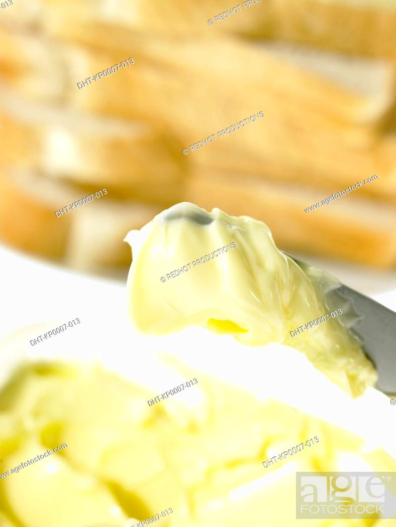 Stock Photo: Bread slices and Butter on a knife.