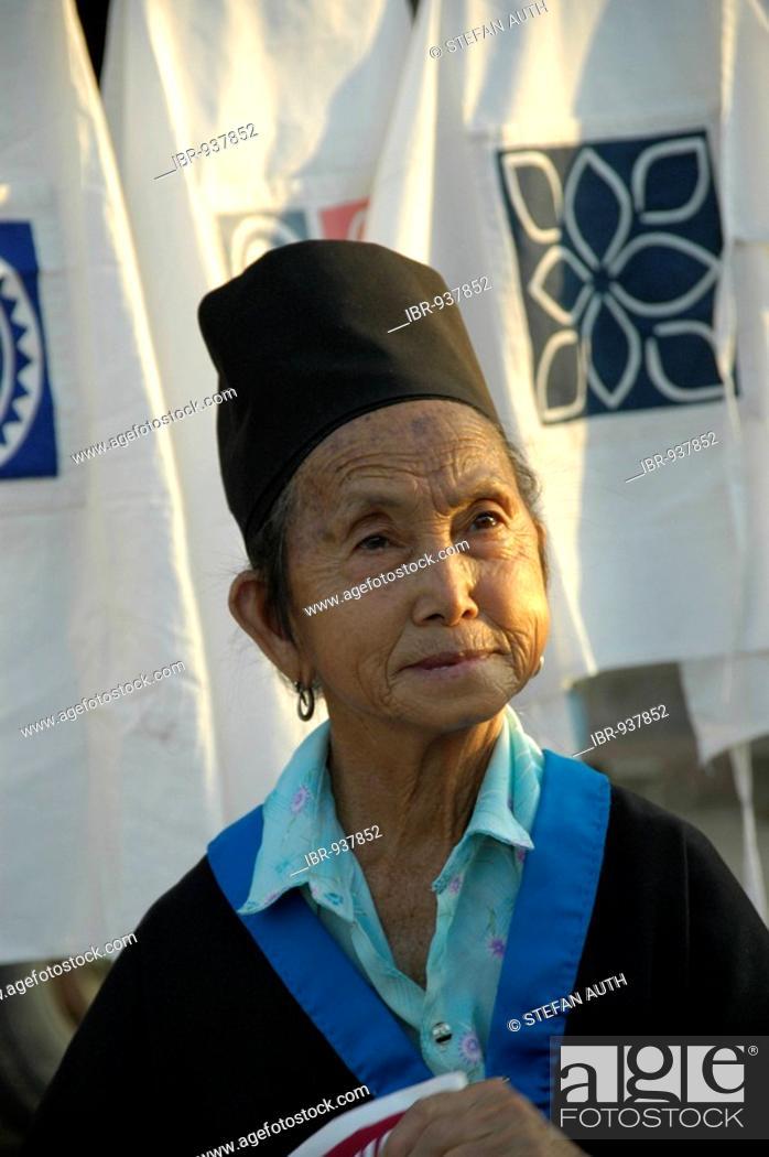 Stock Photo: Old woman wearing traditional dress of Hmong ethnic, selling cloth at the night market, Luang Prabang, Laos.