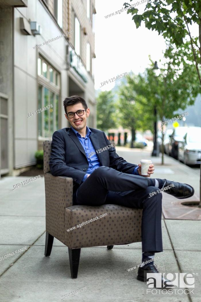 Stock Photo: A young man sits in an armchair on an outdoor walkway and holds a cup of coffee; Bothell, Washington, United States of America.