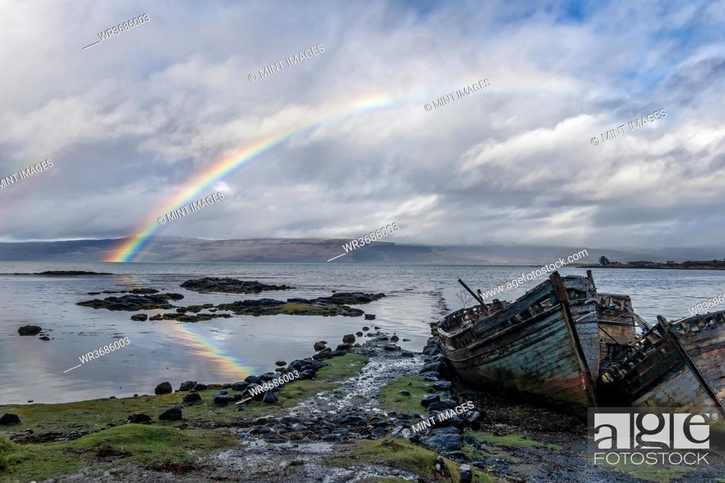 Stock Photo: Rainbow and beached old wooden fishing boats on shore at Salen.
