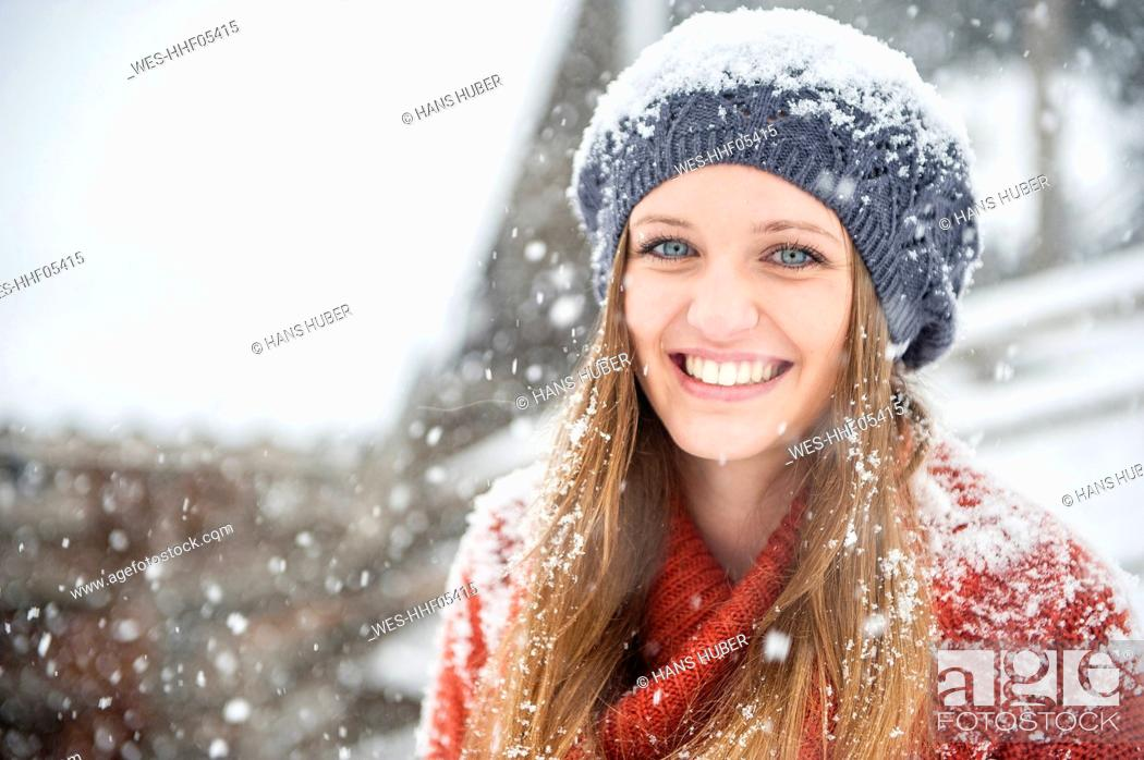 Stock Photo: Portrait of smiling young woman in heavy snowfall.
