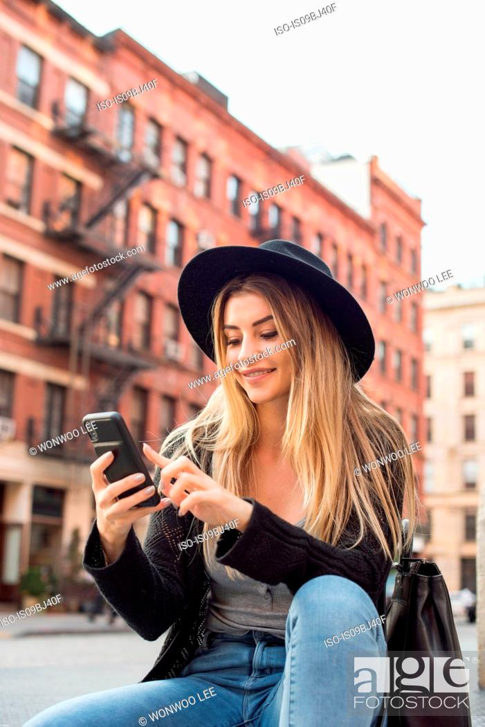 Stock Photo: Woman looking at mobile phone smiling, texting, New York, USA.