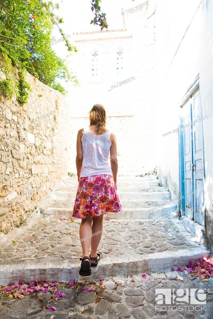 Stock Photo: woman walking up the cars in a Greek village.