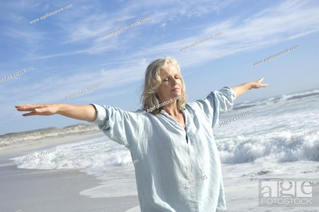 Stock Photo: Woman in yoga attitude on the beach, outdoors.