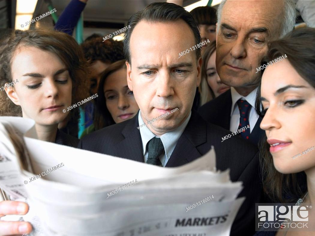 Stock Photo: Commuters standing on train reading newspaper over shoulder.