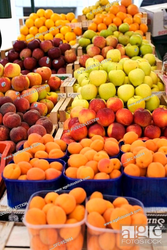 Stock Photo: Fruit stall with apricots, peaches, apples, oranges.