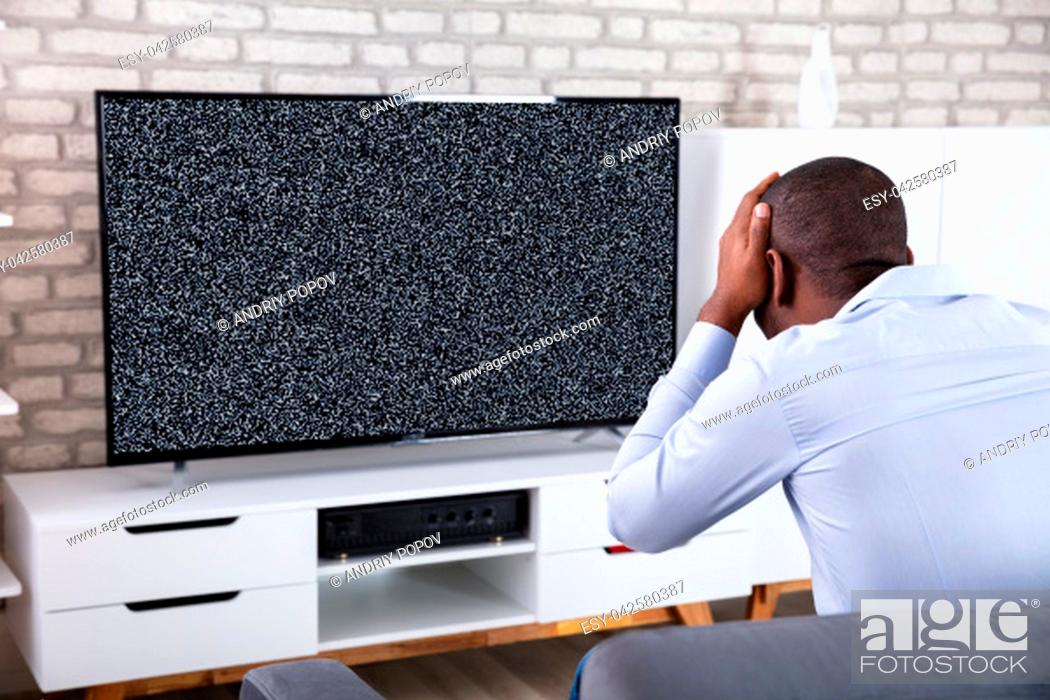Stock Photo: African Man Touching His Head Near Television Showing No Signal.