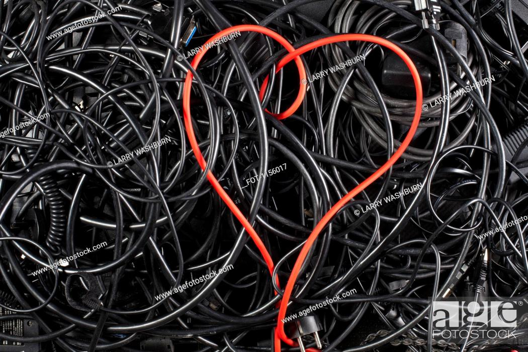 Stock Photo: A red cord in a heart shape amongst tangled black cables and cords.
