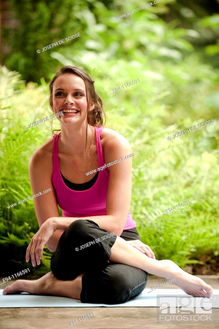 Stock Photo: 25 year old brunette woman in a garden settng wearing work out clothing, sitting on the ground smiling at the camera.