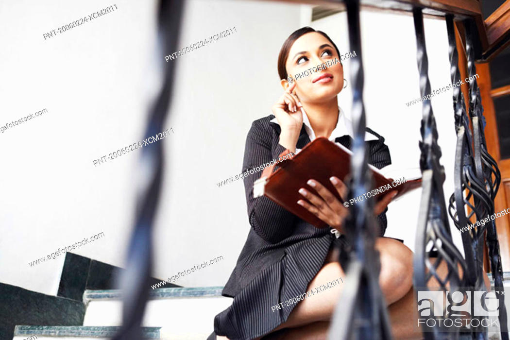 Stock Photo: Businesswoman sitting on the staircase and holding a personal organizer.