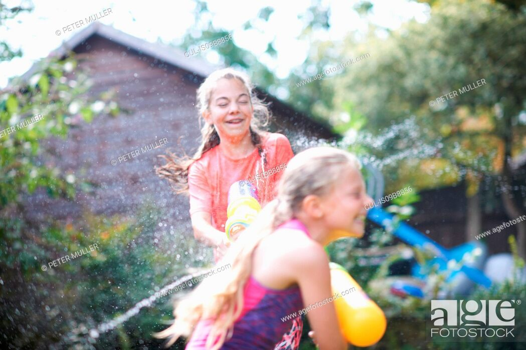 Stock Photo: Teenage girl and her sister squirting water guns at each other in garden.
