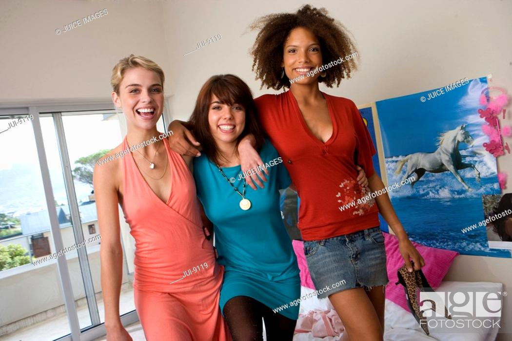 Stock Photo: Three teenage girls 15-17 standing on bed in bedroom, smiling, portrait.