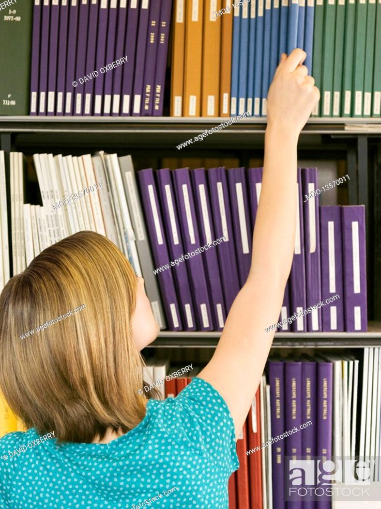 Stock Photo: Young girl reaching for book from library shelf back view.