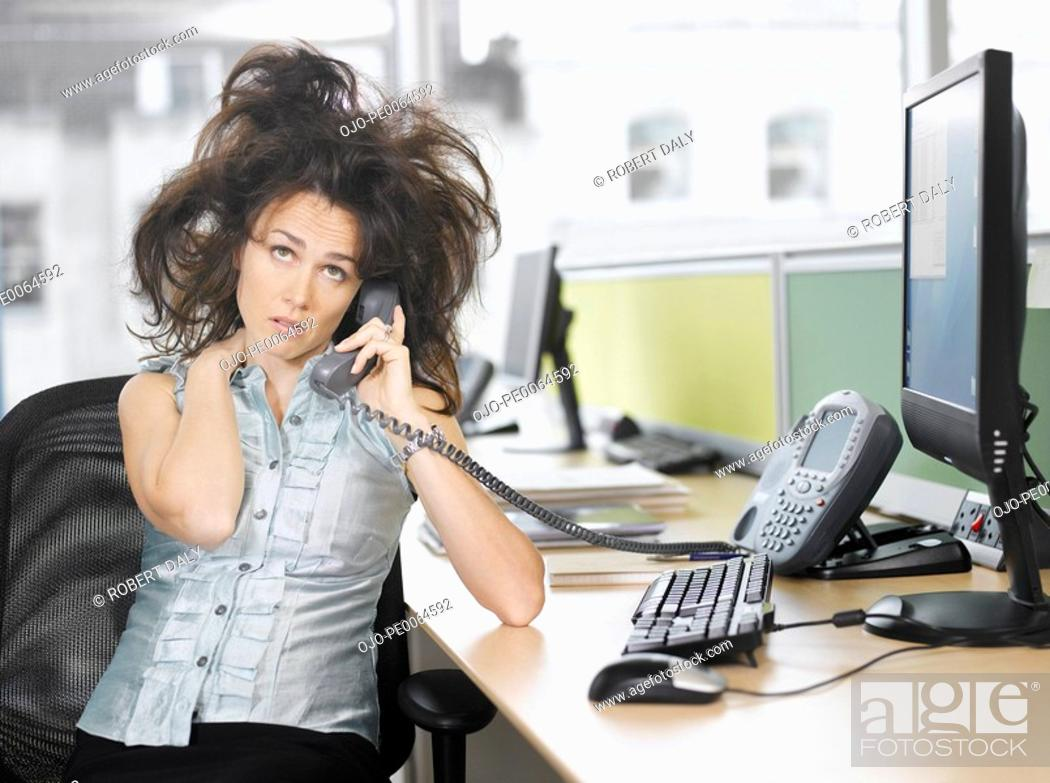 Stock Photo: Frazzled businesswoman talking on telephone.