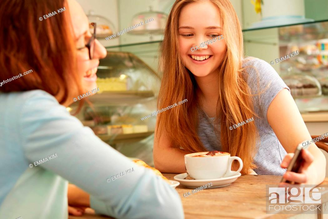 Stock Photo: Friends in cafe looking at smartphone smiling.