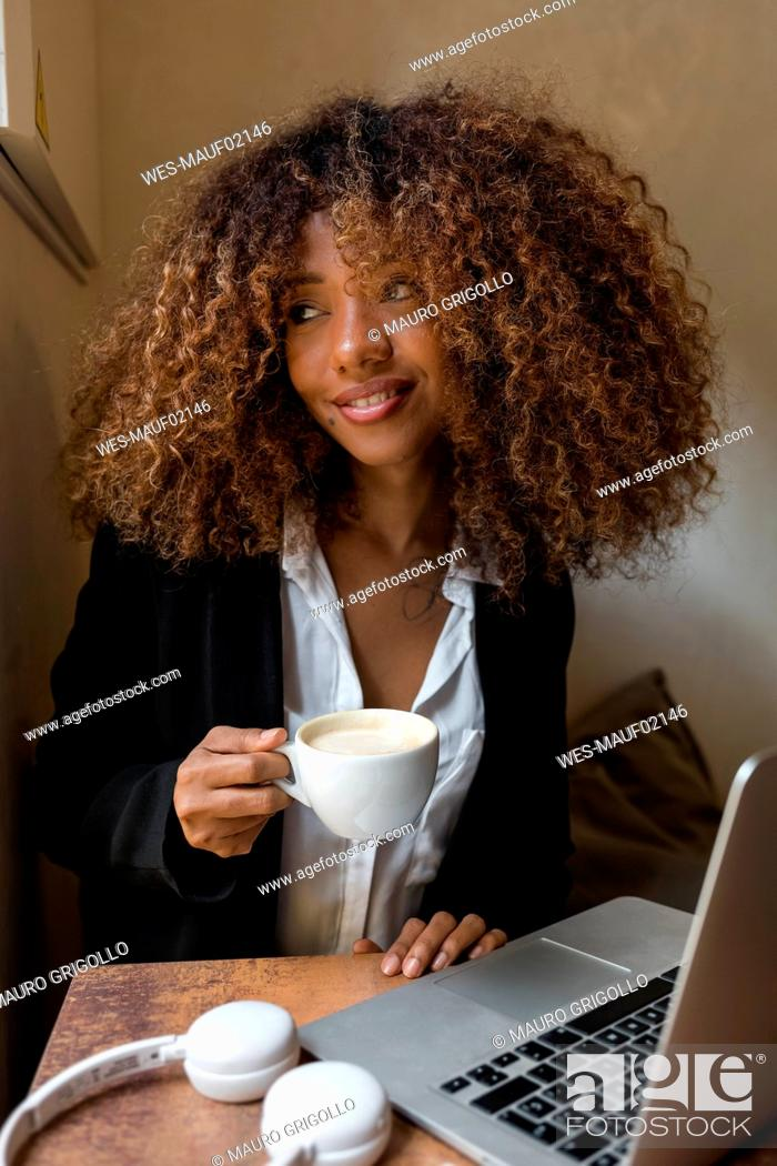 Stock Photo: Young woman with laptop in a cafe, drinking a coffee.