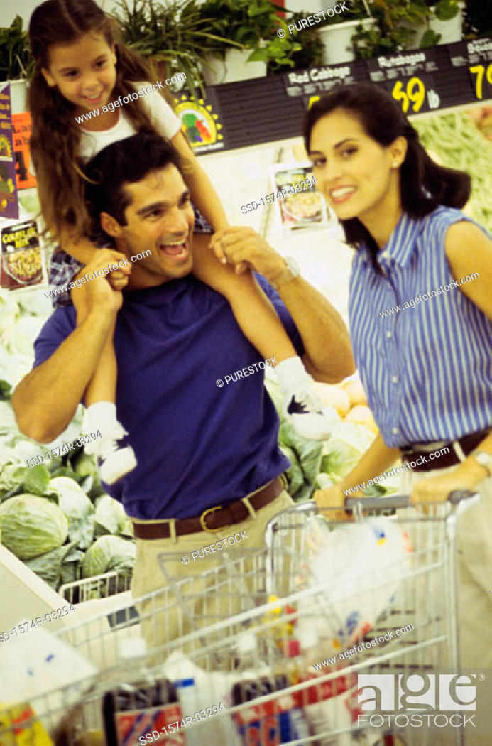 Stock Photo: Parents shopping with their daughter in a supermarket.