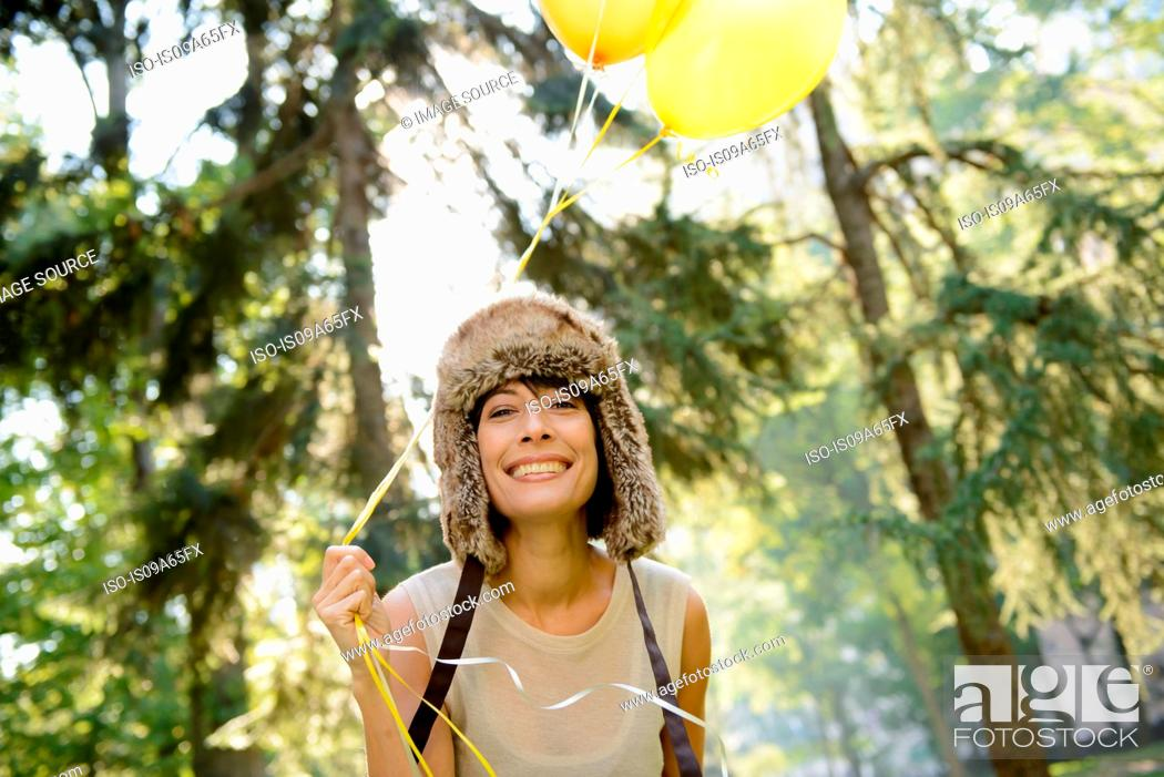 Stock Photo: Woman carrying balloons in park.