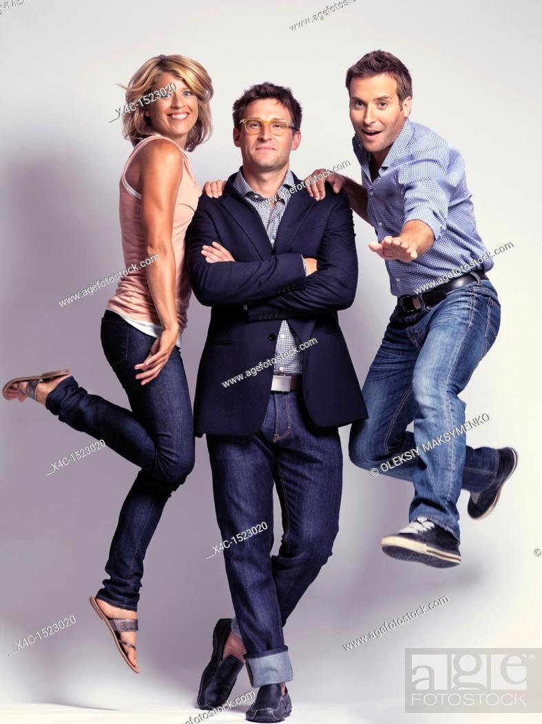 Stock Photo: Artistic portrait of smiling casually but with style dressed two men and a woman wearing jeans.