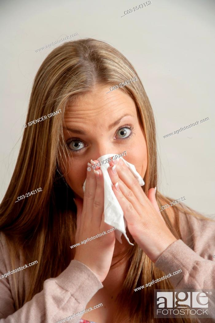 Stock Photo: Using a handkerchief, a young adult woman blows her nose in Laguna Beach, CA. Note Cardigan sweater.