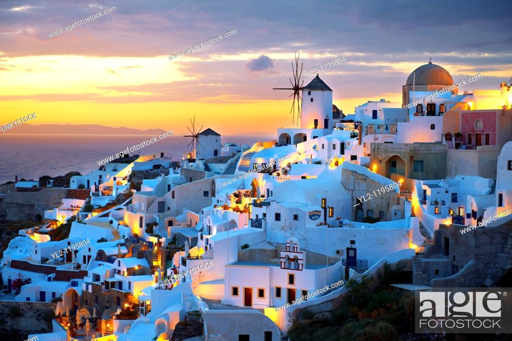 Stock Photo: Oia Ia Santorini - Windmills and town at sunset, Greek Cyclades islands.