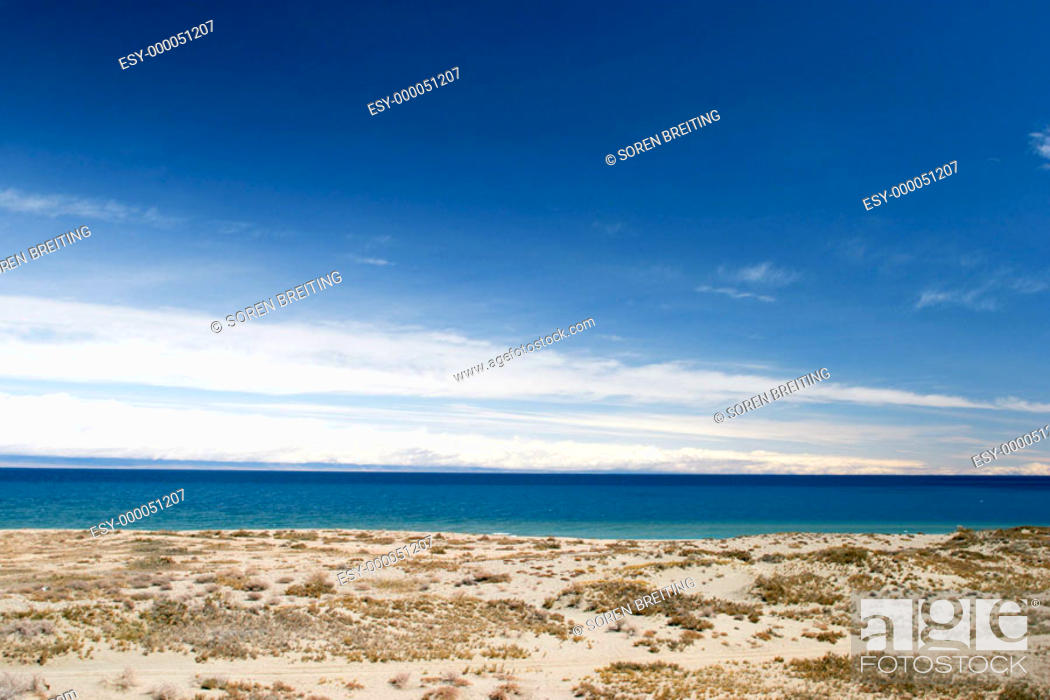 Stock Photo: Issyk-Kul Lake, (Ysyk-köl)  in Kyrgyzstan, Central Asia, seen from southern beach, west of Bökönbaev, with dry lands around with xerophytes and snowclad.