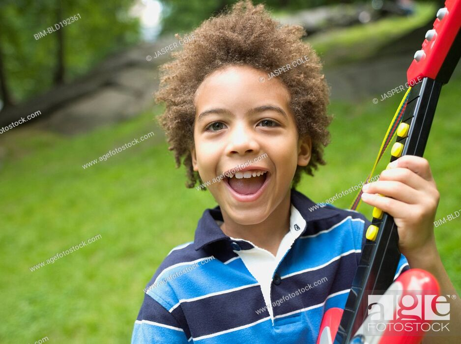 Stock Photo: Mixed race boy with plastic guitar.