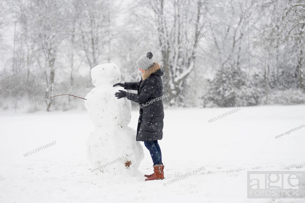 Stock Photo: Germany, woman building snowman.