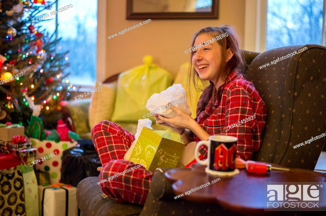 Photo de stock: Young woman opening Christmas present wearing plaid pajamas in Fallston, Maryland, USA.
