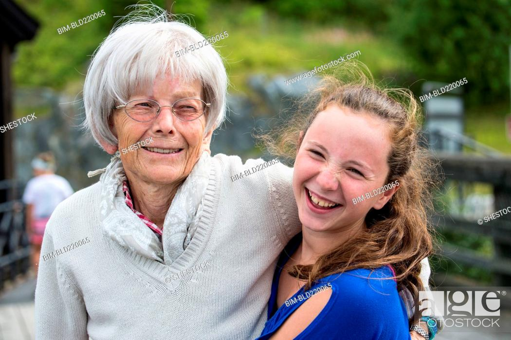 Stock Photo: Grandmother and granddaughter hugging at park.