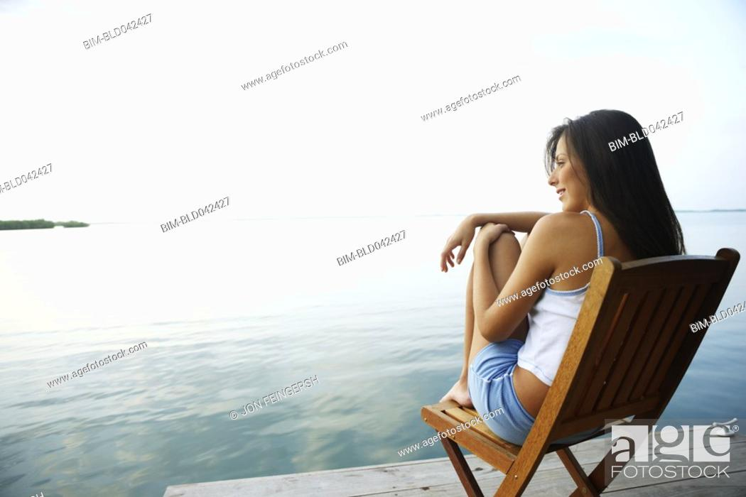 Stock Photo: South American woman in deck chair on dock.