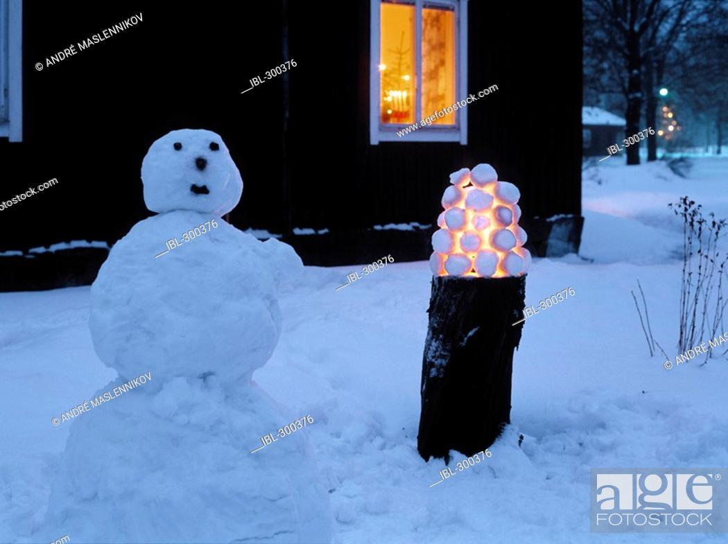 Stock Photo: Snowman and snowball lantern in garden.
