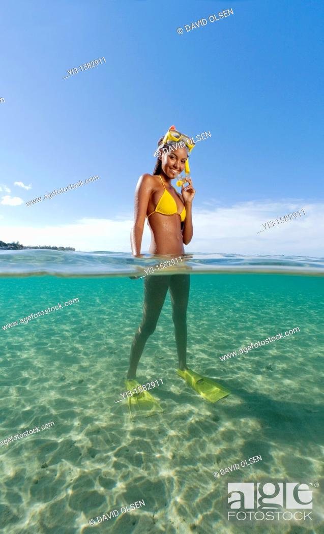 Stock Photo: Over and underwater view of smiling girl with snorkel, mask, and fins at Lahaina, Maui, Hawaii.