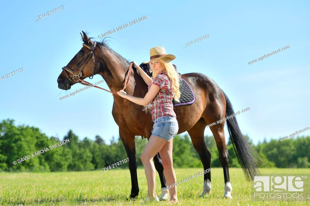 Stock Photo: Young cowgirl with a polish arabian horse standing on a meadow.