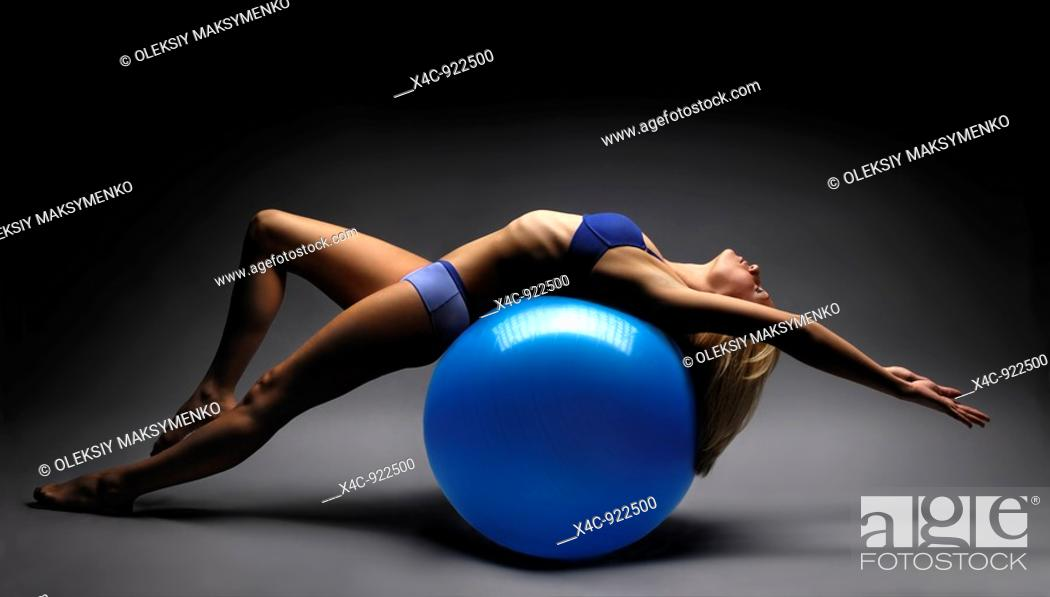 Stock Photo: Artistic photo of a woman balancing on exercise ball.