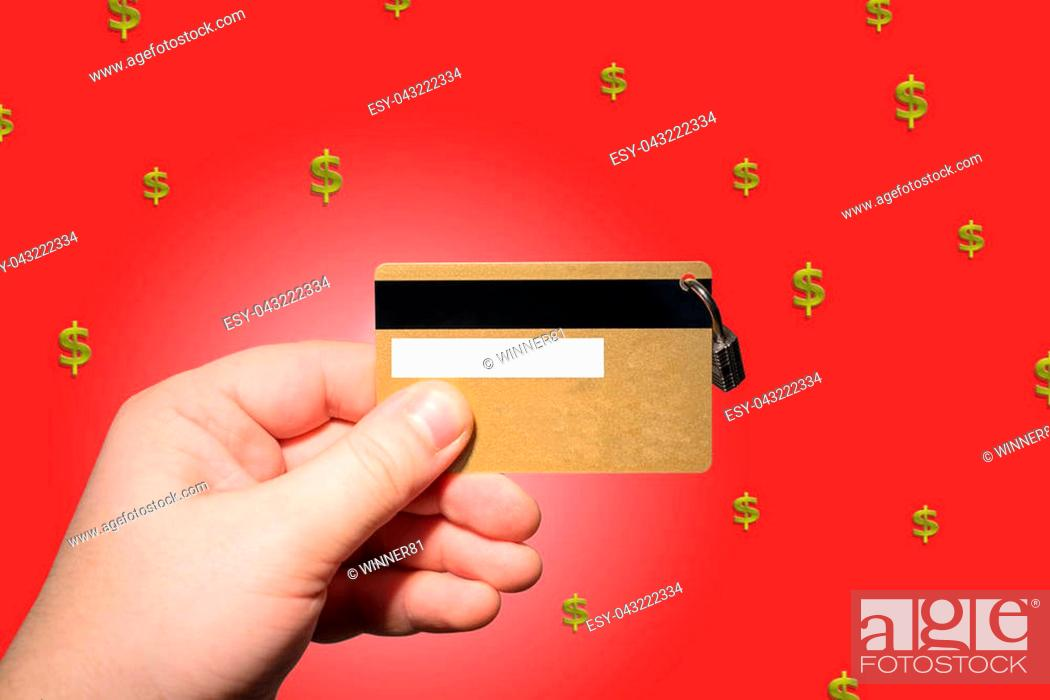 Photo de stock: hand holding credit card on the red background and golden rain.