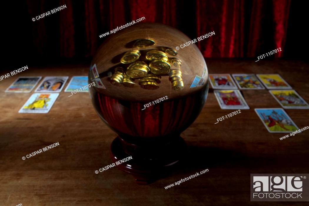 Stock Photo: A crystal ball with gold coins in the reflection and tarot cards in background.