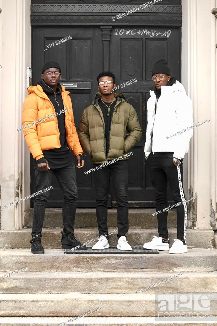 Imagen: three stylish male friends standing on stairs in front of door, in city Munich, Germany.