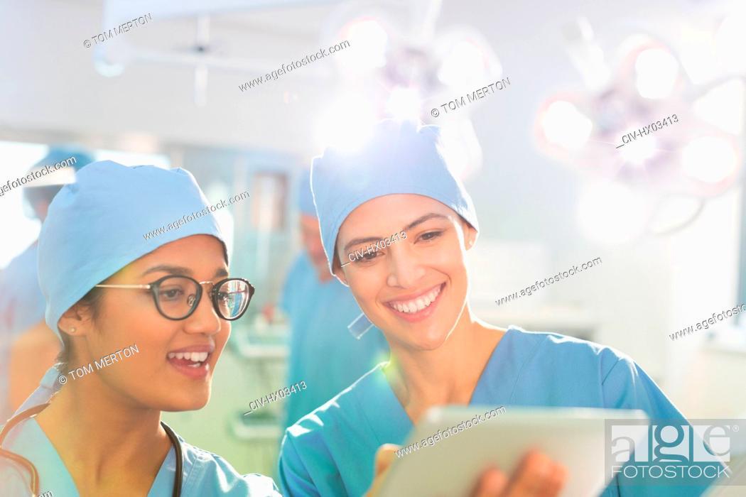 Stock Photo: Female surgeons using digital tablet, talking in operating room.