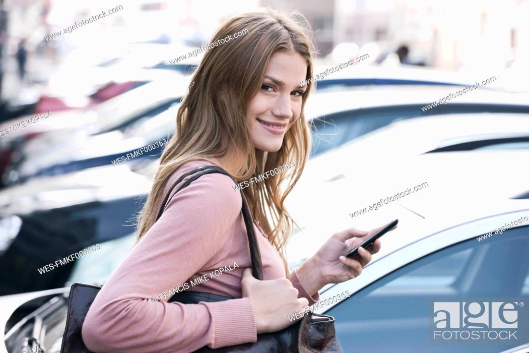 Stock Photo: Germany, Cologne, Young woman with phone near parking lot, smiling, portrait.